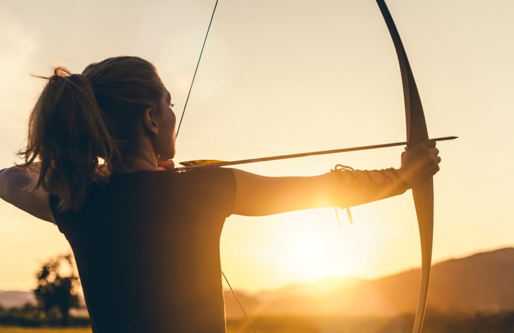 Woman with a bow and arrow aiming, sunlight behind- Are we in control?