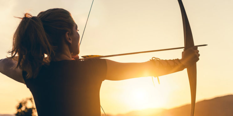 Woman with a bow and arrow aiming, sunlight behind