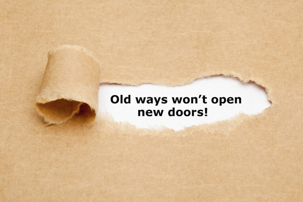 Inspirational quote Old Ways Will Not Open New Doors typed on vintage typewriter.
