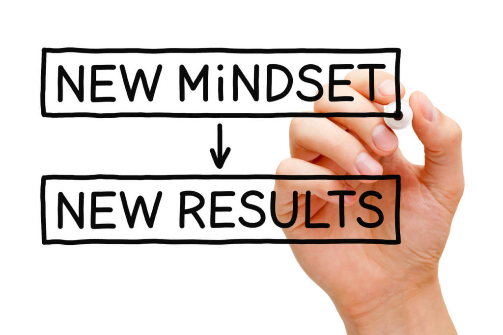 Hand writing New Mindset New Results with black marker on transparent wipe board.