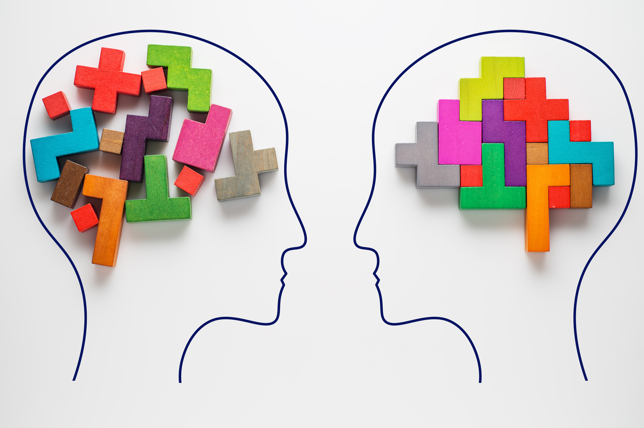 Investor Biases: Heads of two people with colourful shapes of abstract brain for concept of idea and teamwork.