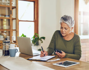 woman planning her retirement finances with pen, paper, and laptop